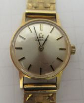 A lady's Omega 9ct gold cased wristwatch, faced by a baton dial, on a 9ct gold flexible strap