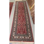 """A Persian runner, decorated with floral motifs, on a red and blue ground 134"""" x 33"""""""
