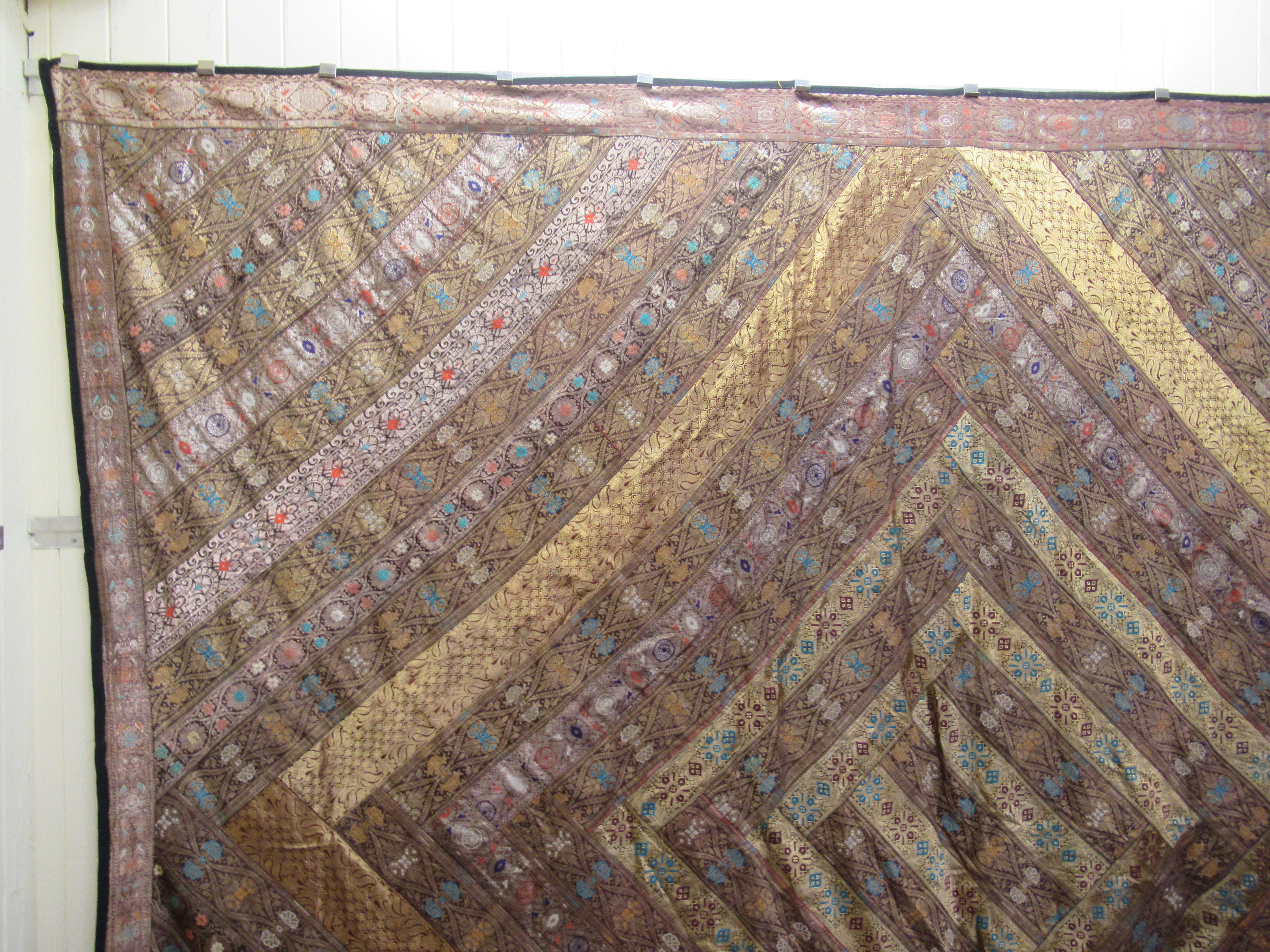 An Indian part silk bed throw, profusely decorated with repeating floral designs with a black fabric - Image 4 of 7