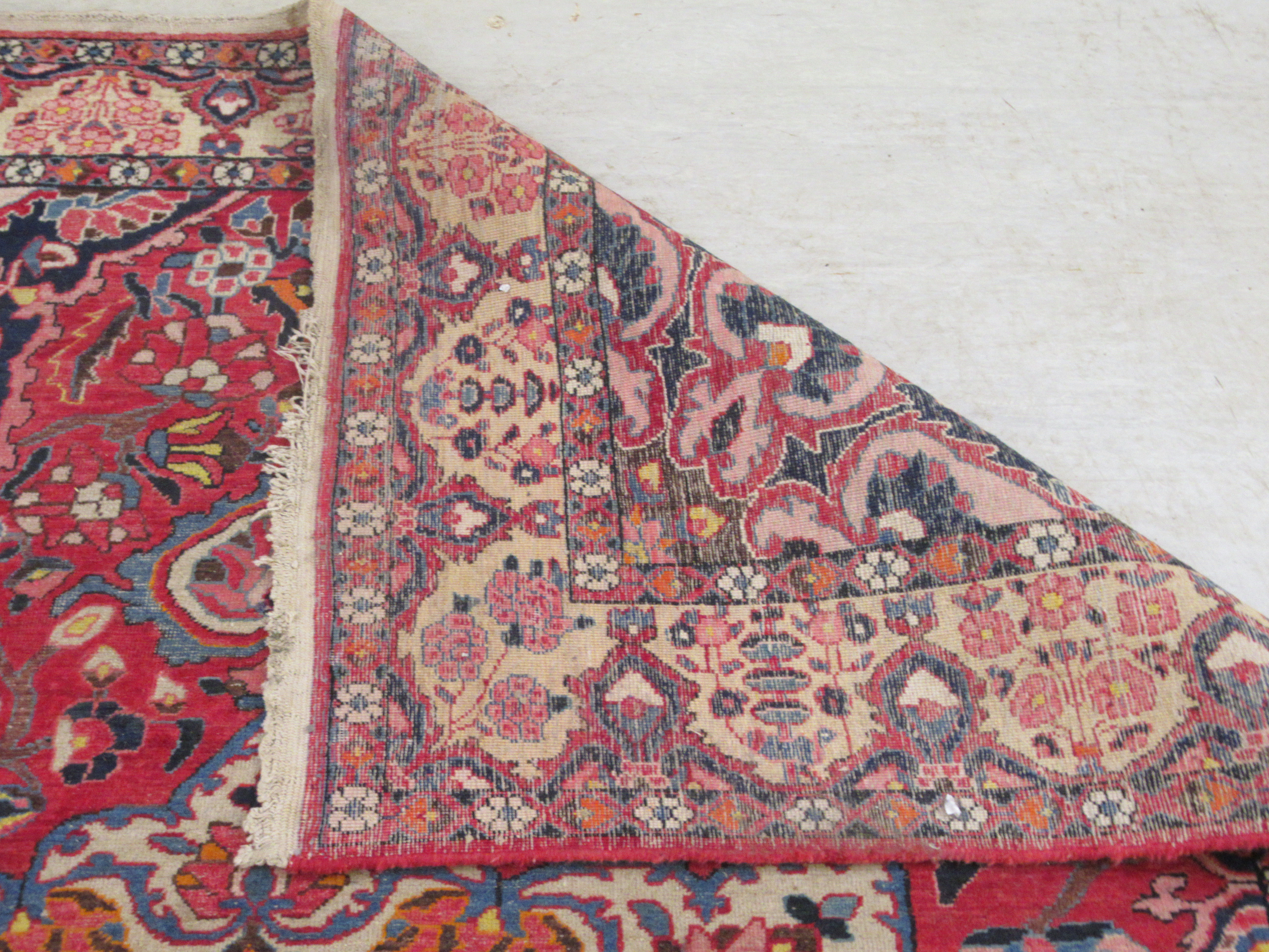 A Persian carpet, profusely decorated with flora and other designs, on a multi-coloured and red - Image 5 of 5