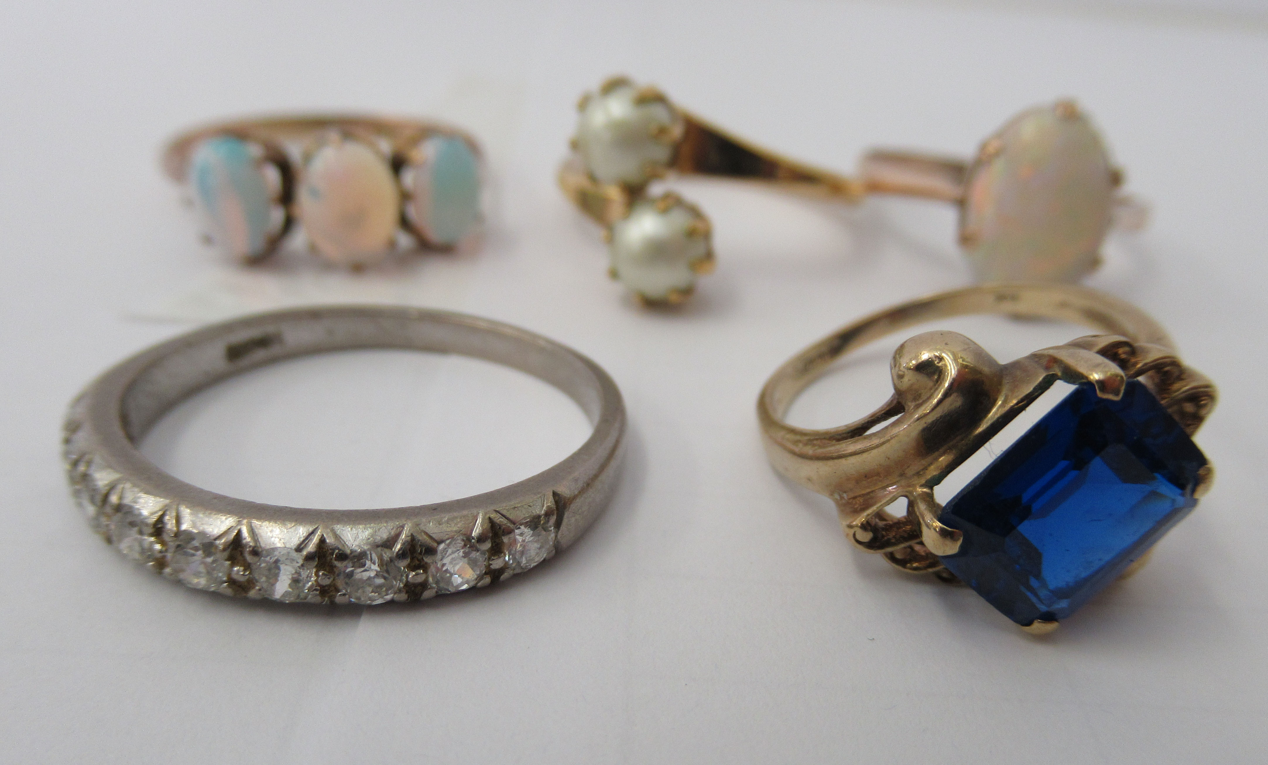 Three yellow metal rings and a white metal coloured ring, set with simulated pearls, opals and other