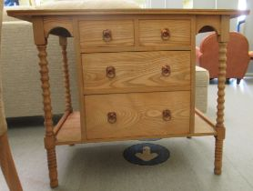 An Edwardian style light oak washstand with two short/two long central drawers, flanked by