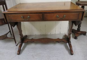 A 20thC walnut finished sofa table, the top with fall flaps, over two frieze drawers, raised on lyre