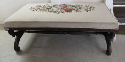 A William IV mahogany framed stool with a floral tapestry upholstered top, raised on arched