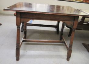 An early 20thC Arts & Crafts inspired occasional table, raised on splayed, turned and block legs