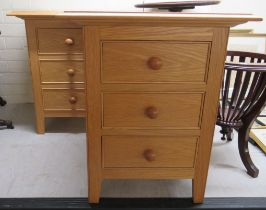 """A pair of modern light oak three drawer bedside chests, raised on square, tapered feet 24""""h 20""""w"""