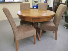"""A modern light oak pedestal dining table 31""""h 43""""dia extending to 56""""w with an integral leaf;"""