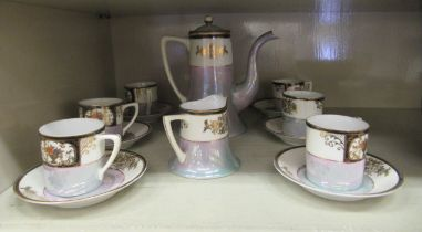 A Noritake porcelain coffee set comprising six place settings, a coffee pot and cream jug