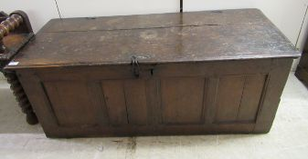 """An early 18thC oak coffer, the planked hinged lid, over a four panelled front 20""""h 51""""w"""