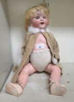 """A German bisque head porcelain doll with composition limbs and fabric clothes 19""""h"""
