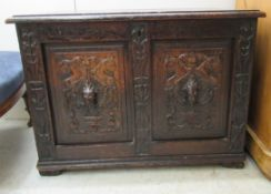 A late Victorian oak coffer with a hinged lid, over a twin panelled front and carved mask motifs, on
