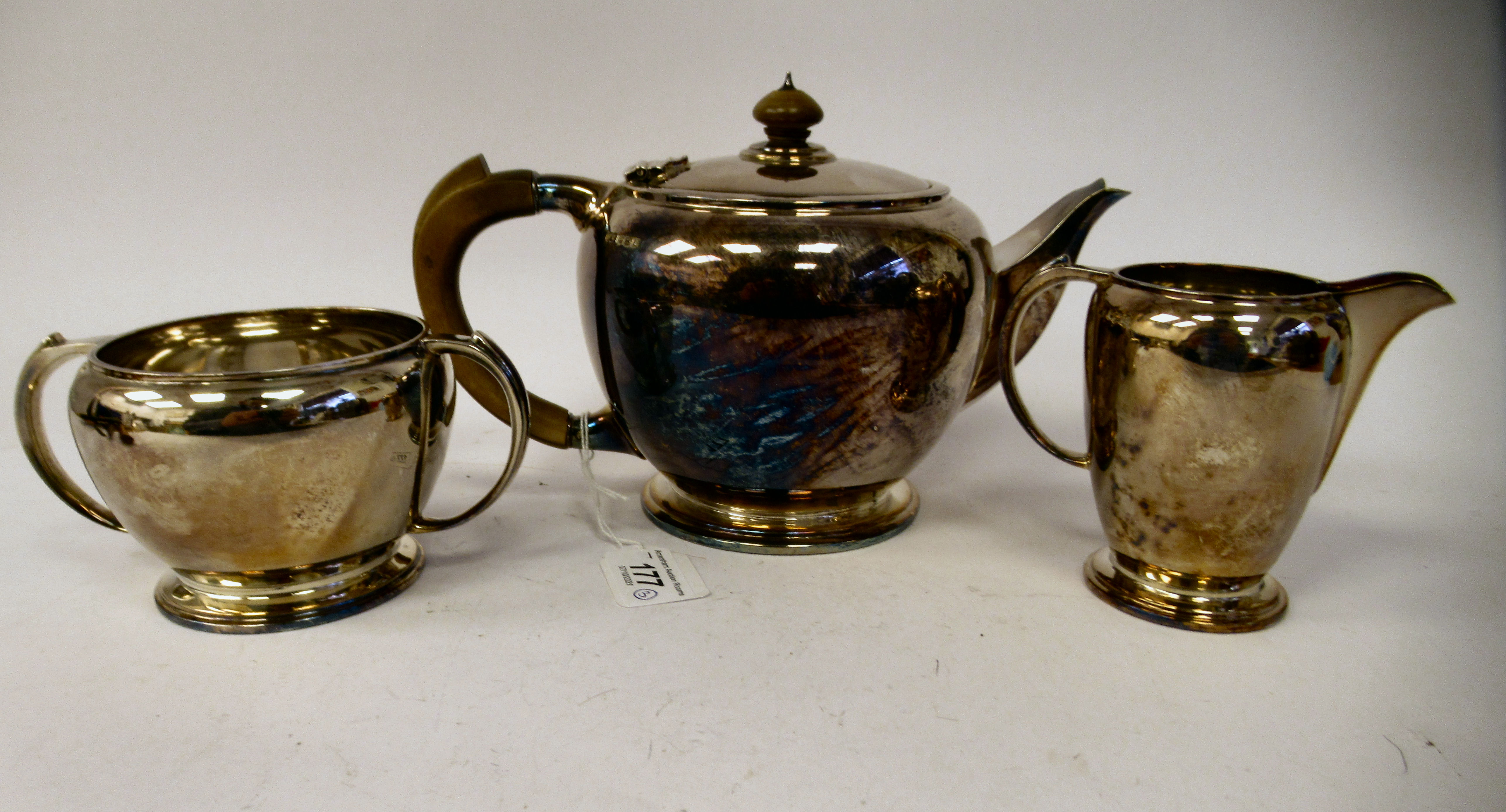 A three piece silver tea set of bulbous form, comprising a teapot with a short spout, an insulated