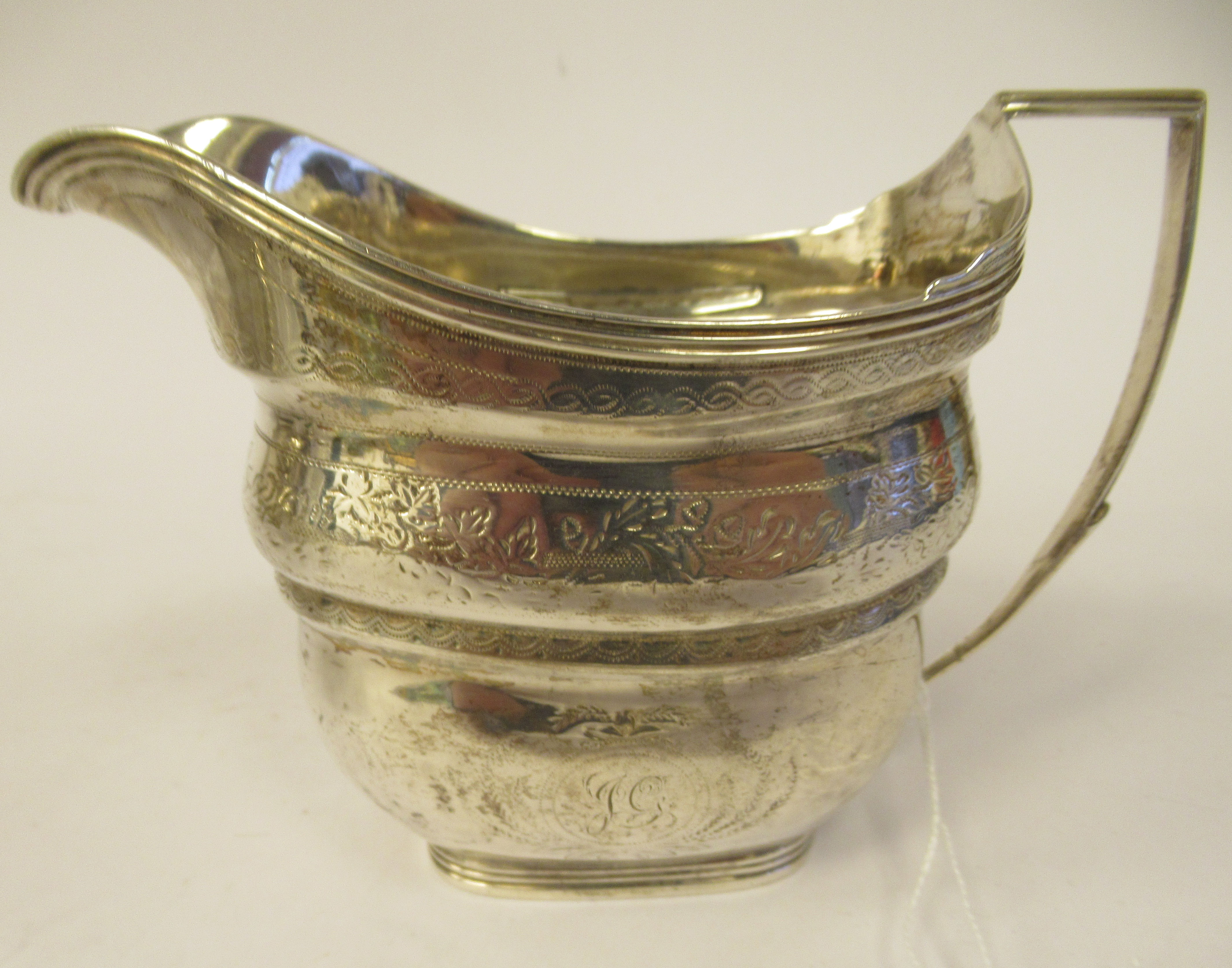 A late 18th/early 19thC silver cream jug of stepped and tapered rectangular outline with bands of