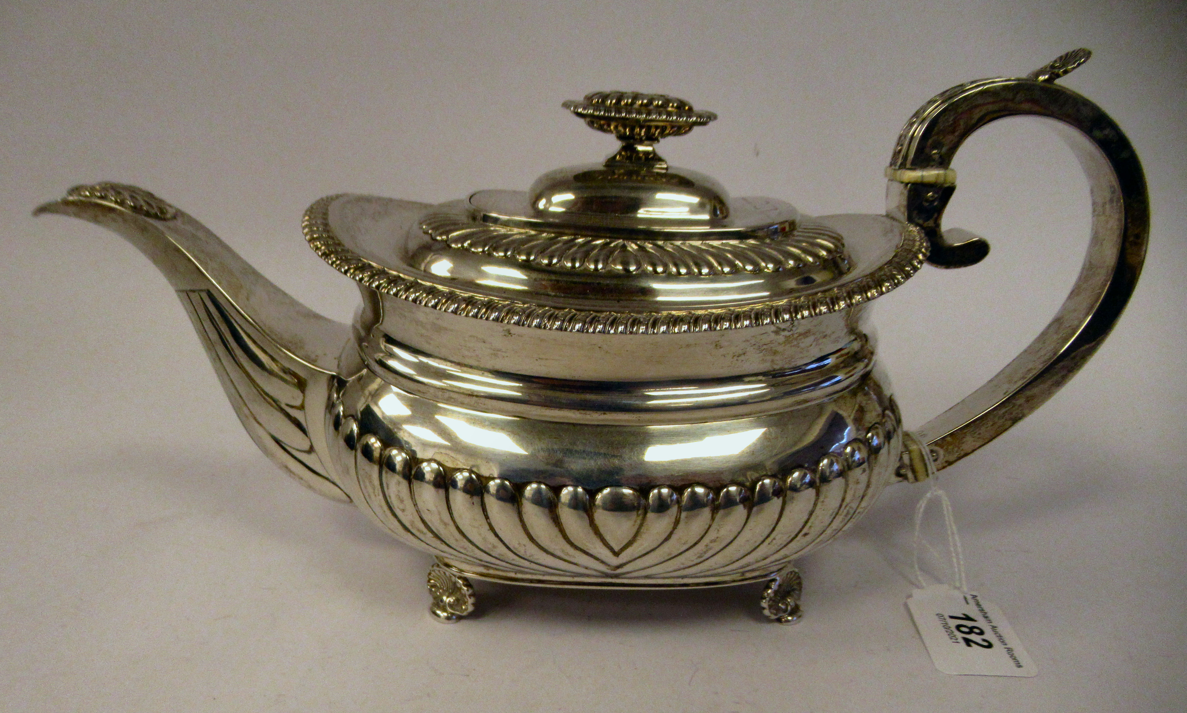 A George III silver teapot of squat, bulbous circular form with floral and foliate cast ornament,