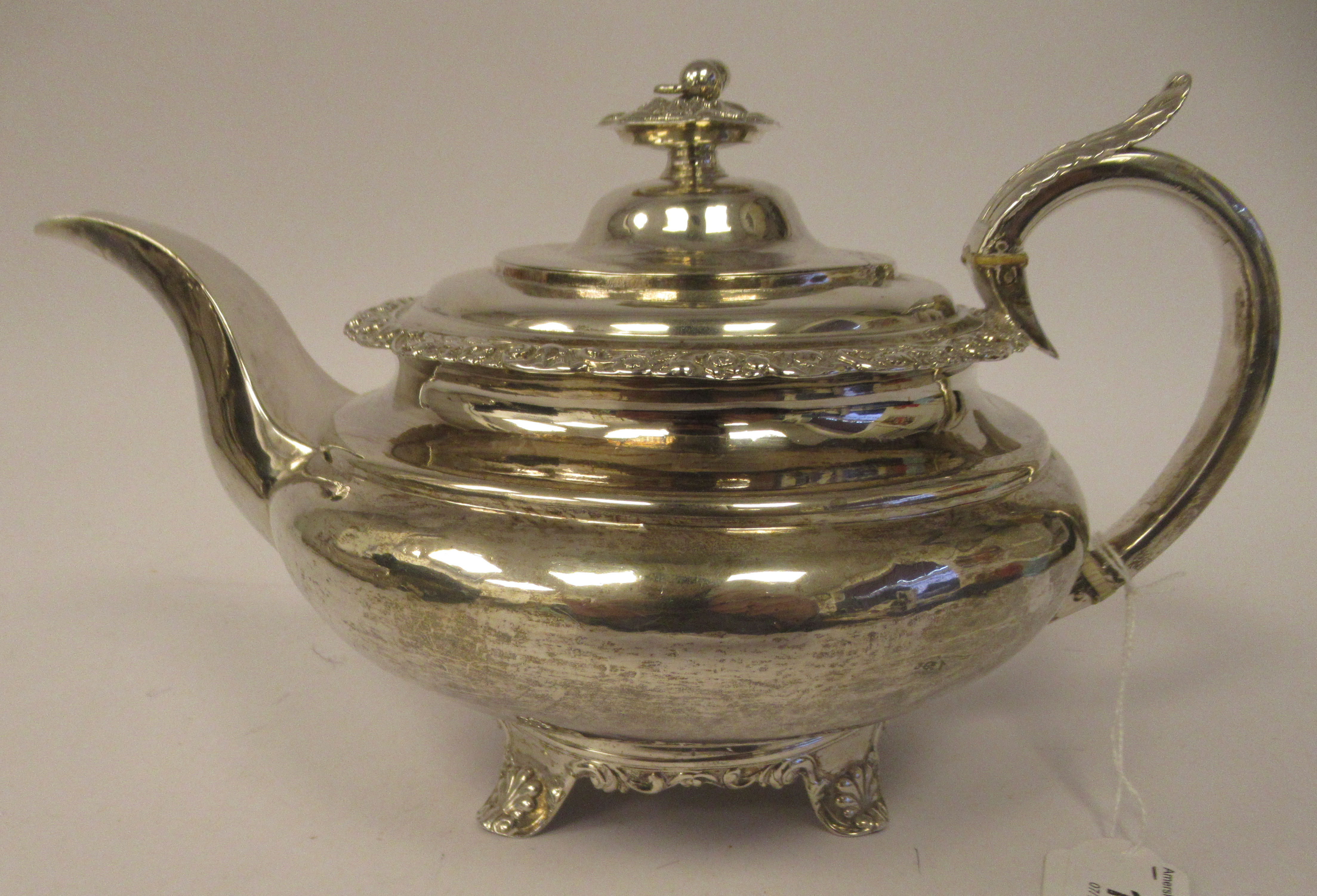 A George III silver teapot of demi-reeded squat, bulbous, oval form with gadrooned and cast