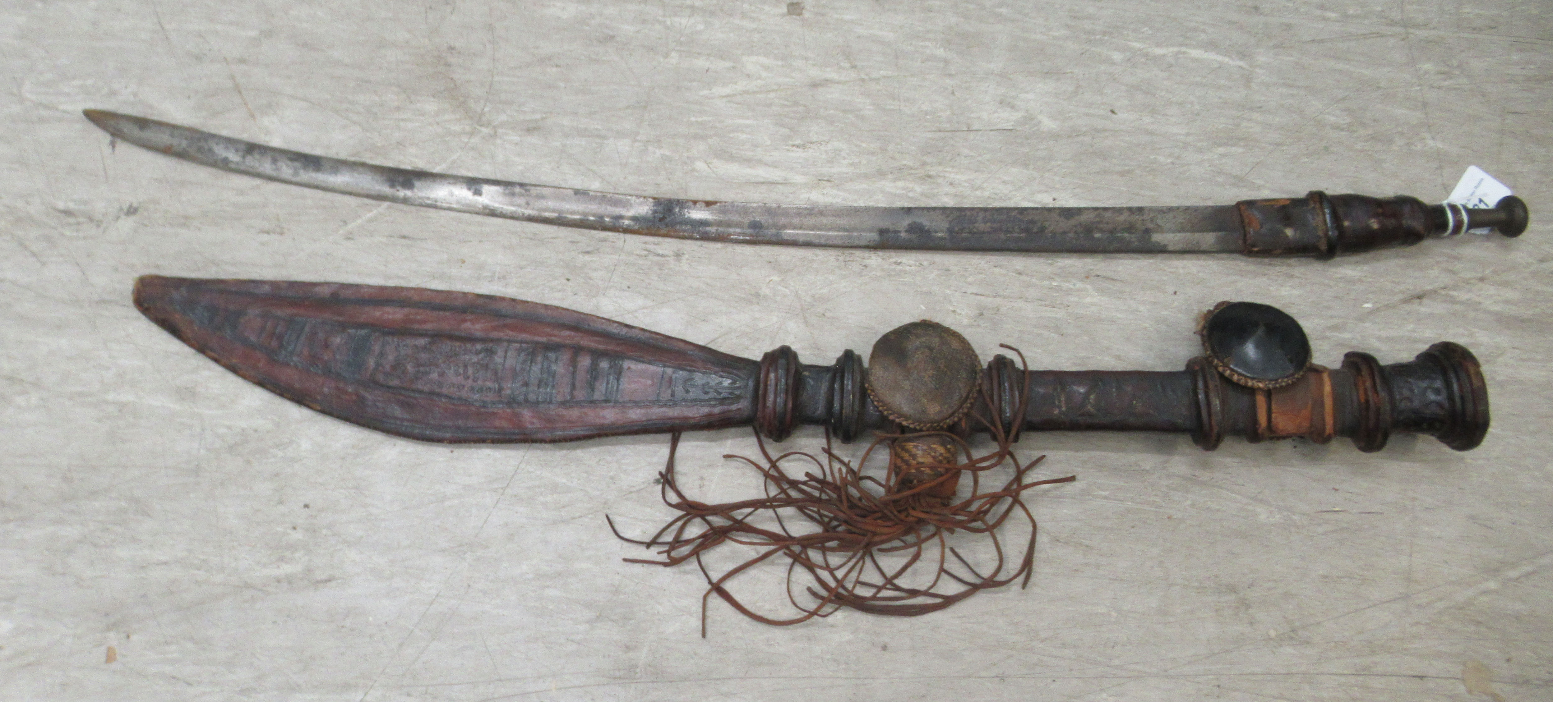 A late 19thC Islamic Tuareg Mandingo sword with a brown hide handle and decorative scabbard the