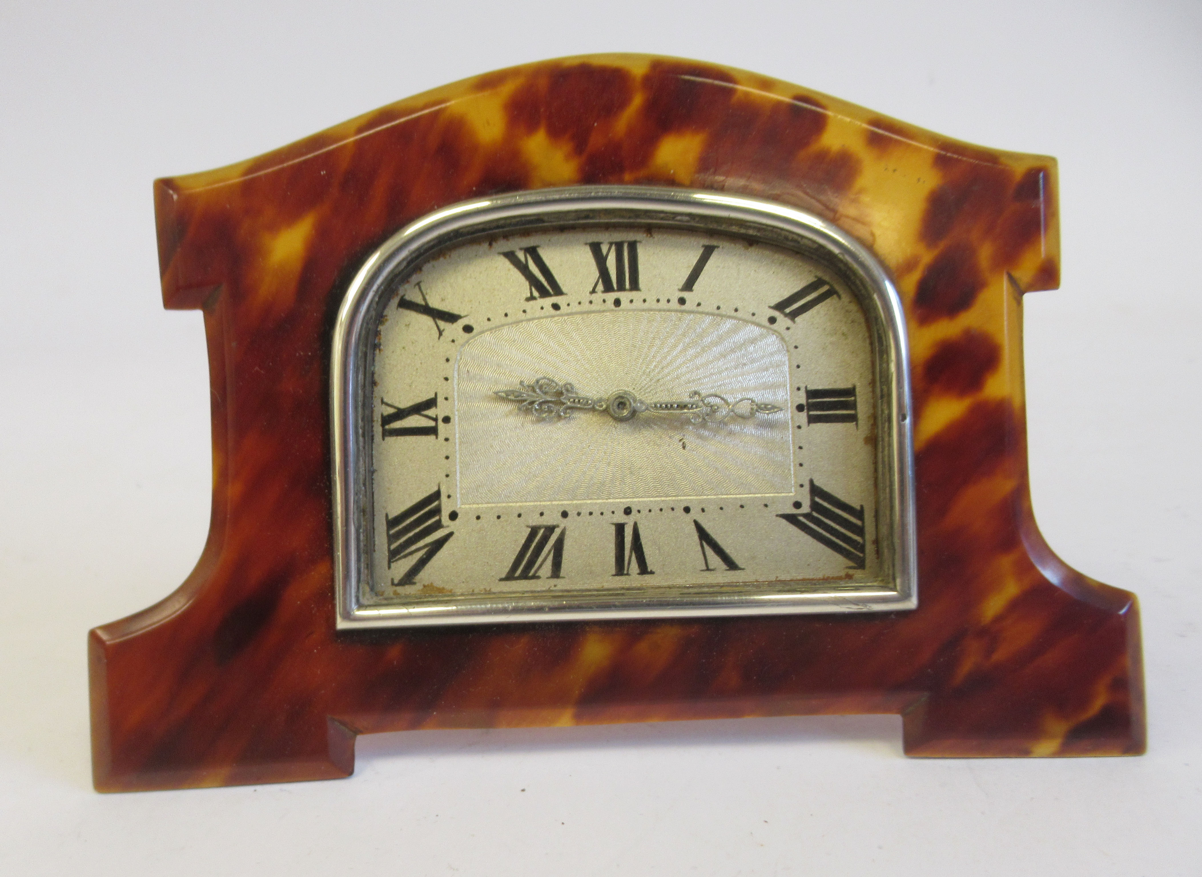 An Art Deco silver coloured metal cased mantel timepiece, set in a shaped tortoiseshell surround, on