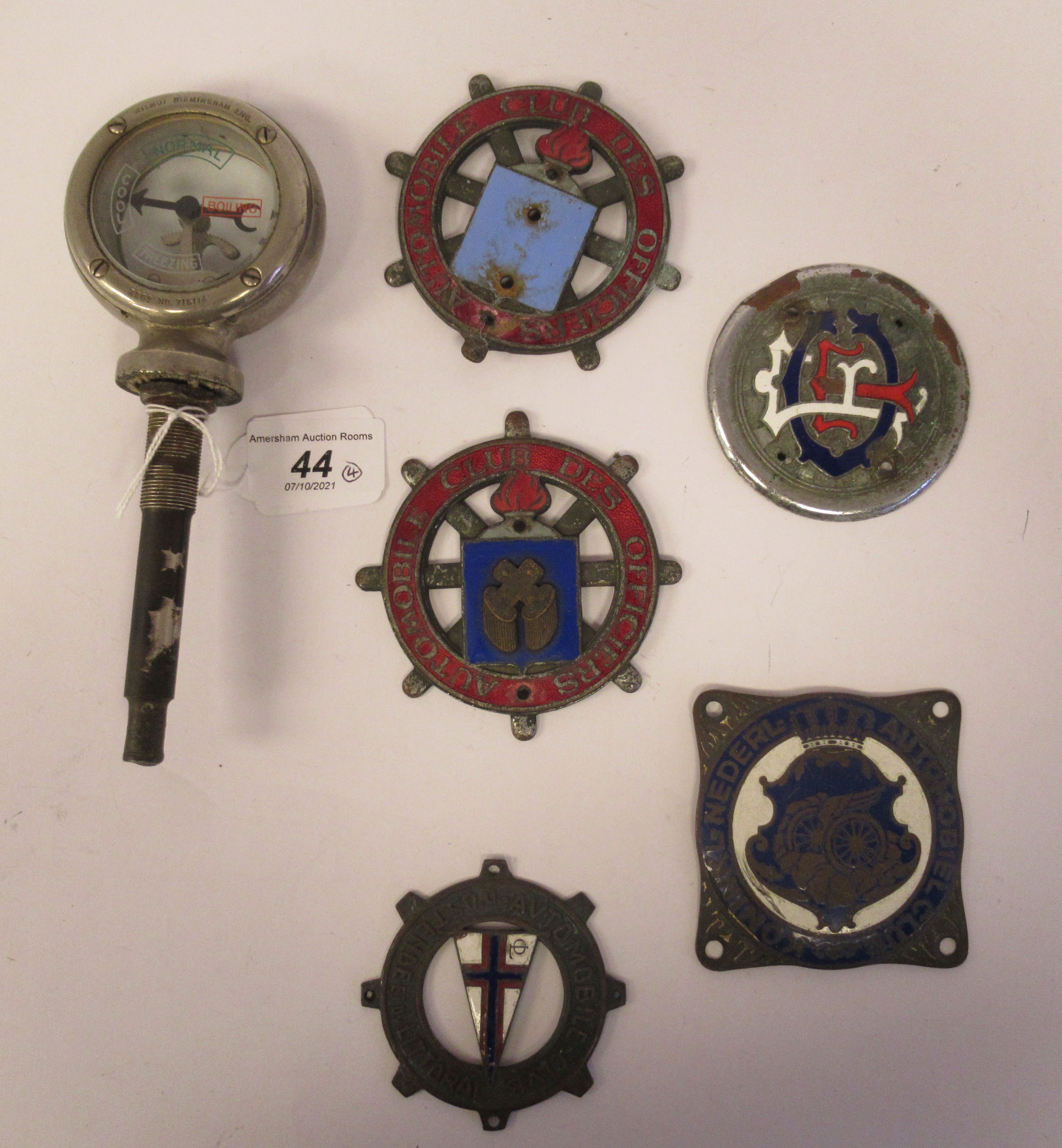 Five early 20thC Continental European coloured enamel motoring related badges; and a car mascot