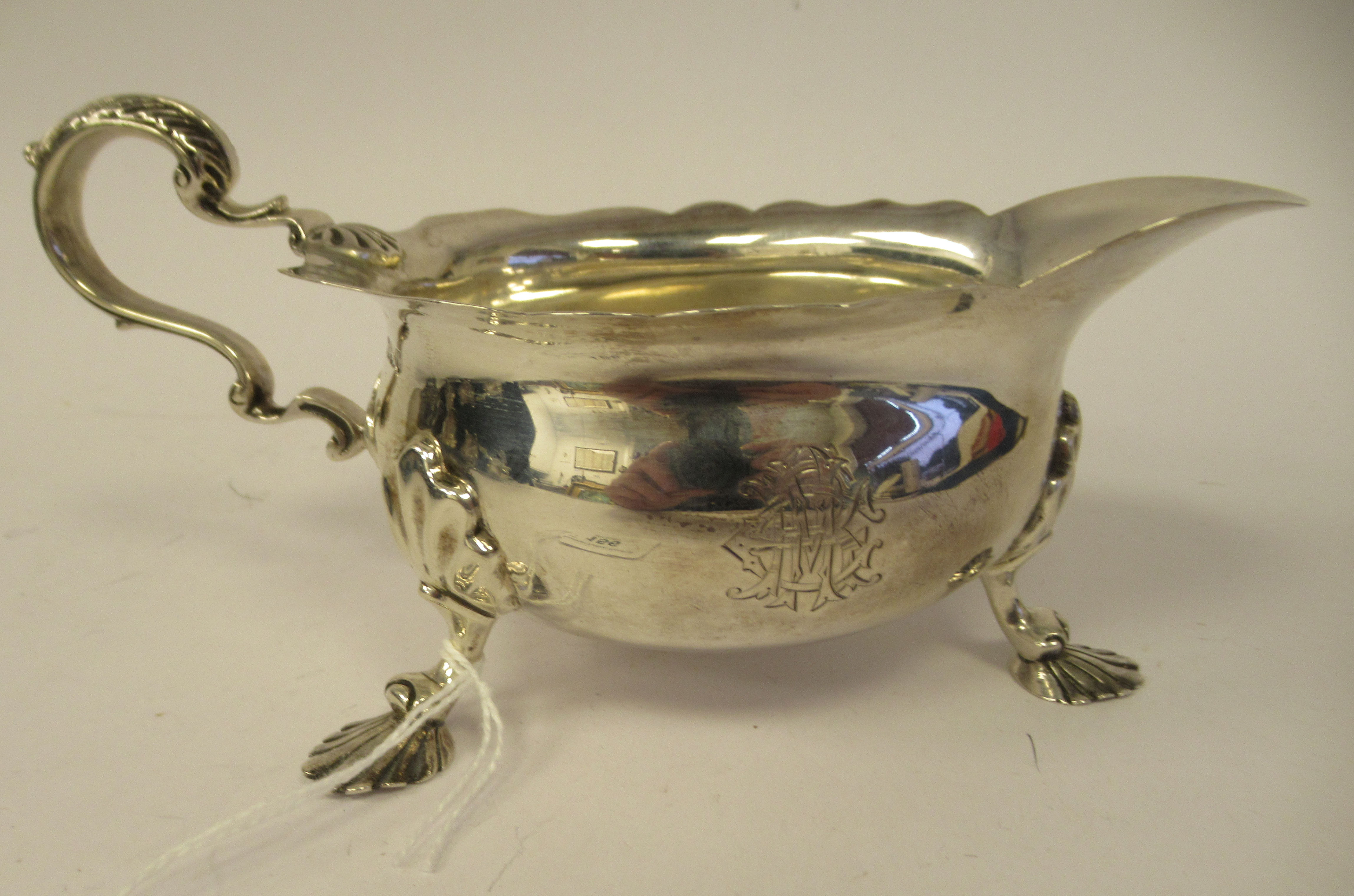 An Edwardian silver sauce boat with a decoratively cut, flared, wavy rim, a shell and acanthus, C-