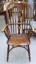 A 19thC Windsor beech and elm framed high hoop, spindled and splat back arm chair, the solid seat