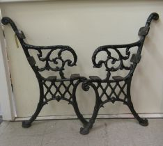 A pair of Victorian style black painted cast iron bench ends