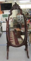 A late Victorian/Edwardian mahogany framed cheval mirror, the oval plate within an ornately carved