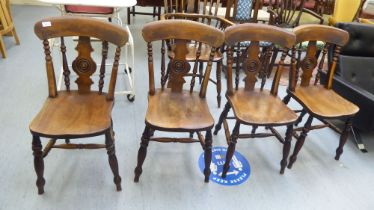 A set of four late Victorian beech and elm framed Windsor chairs, each with a spindled and roundel