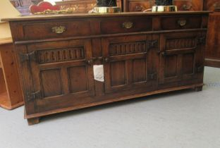 A Titchmarsh & Goodwin Old English style carved and panelled oak sideboard, comprising three