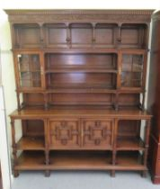 An early/mid 20thC carved oak dresser, the panelled back superstructure with glazed panelled doors