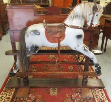 An early 20thC painted dappled grey nursery rocking horse with a studded hide saddle, tail and mane,