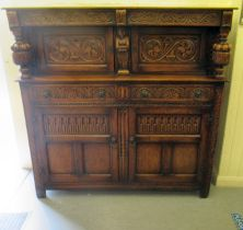 A 1920s/30s carved oak court cupboard, the frieze drawer over a pair of recessed doors and outset