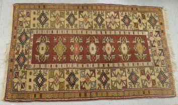 """A patterned wool rug with geometric ornament, on an iron red ground 60"""" x 40"""""""