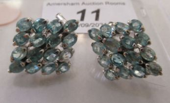 A pair of silver coloured metal earrings, set with multiple blue stones stamped 925
