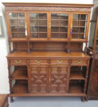 A mid 20thC carved oak dresser, the panelled back and pillared superstructure with four inline