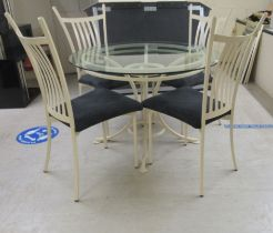 """A modern cream painted metal table with a glass top, raised on splayed legs 30""""h 43""""dia; and a set"""
