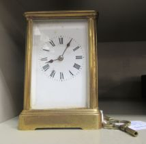 An early 20thC lacquered brass cased carriage clock with bevelled glass panels and a folding top