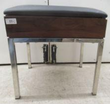 A modern Bentley Design UK stool, the cushioned black vinyl seat over a teak finished panel,