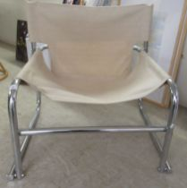 A modern chair, the chromium plated tubular steel frame with a cream coloured canvas sling back