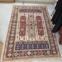 """A Caucasian rug, decorated with repeating stylised designs, on a multi-coloured ground 58"""" x 88"""""""