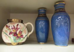 A pair of Royal Doulton sponged blue glazed and gilded baluster shaped vases with flared rims,