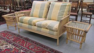 A modern faux bamboo framed two person conservatory settee; and a pair of glazed top lamp tables