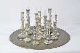 Twelve assorted candlesticks on Indian style tray.