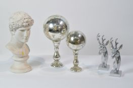 Two globe-style ornaments; two stag's head ornaments; and a bust ornament.