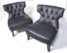 A pair of designer faux black leather easy chairs.