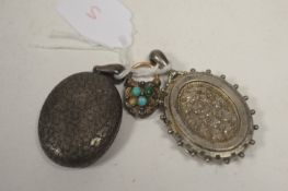 A heart-shaped locket; and two silver oval lockets.