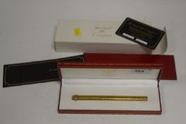 A Must de Cartier gold-painted ballpoint pen.