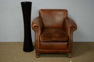 20th C brown leather armchair; and a black glass vase.