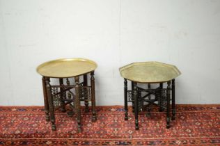 A pair of Islamic brass topped side tables.