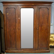 A Victorian mahogany three-door wardrobe, the projecting cornice above a central bevelled mirror