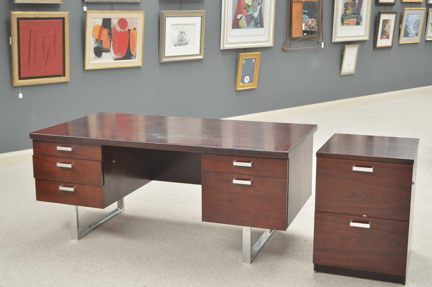 Trevor Chinn for Gordon Russell: a rosewood and chromed metal pedestal desk and filing cupboard.